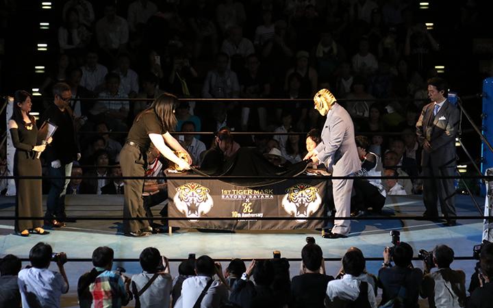 純金マスクにかぶされた布の両端を持つ初代タイガーと、中村之洋