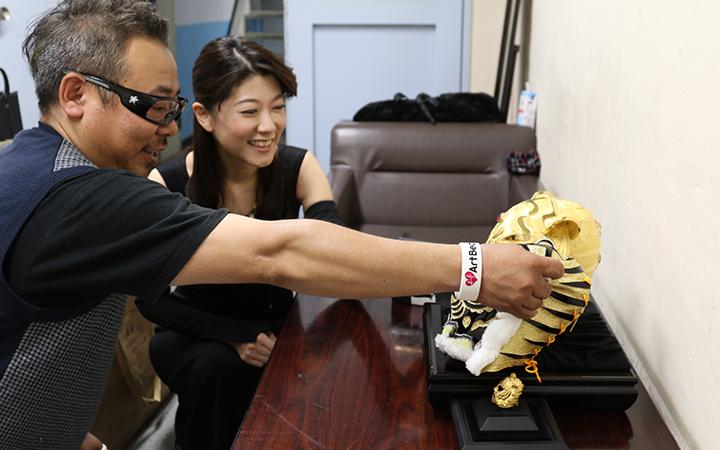 純金マスクを前に談笑する大橋ひろこさんと、川野悟さん